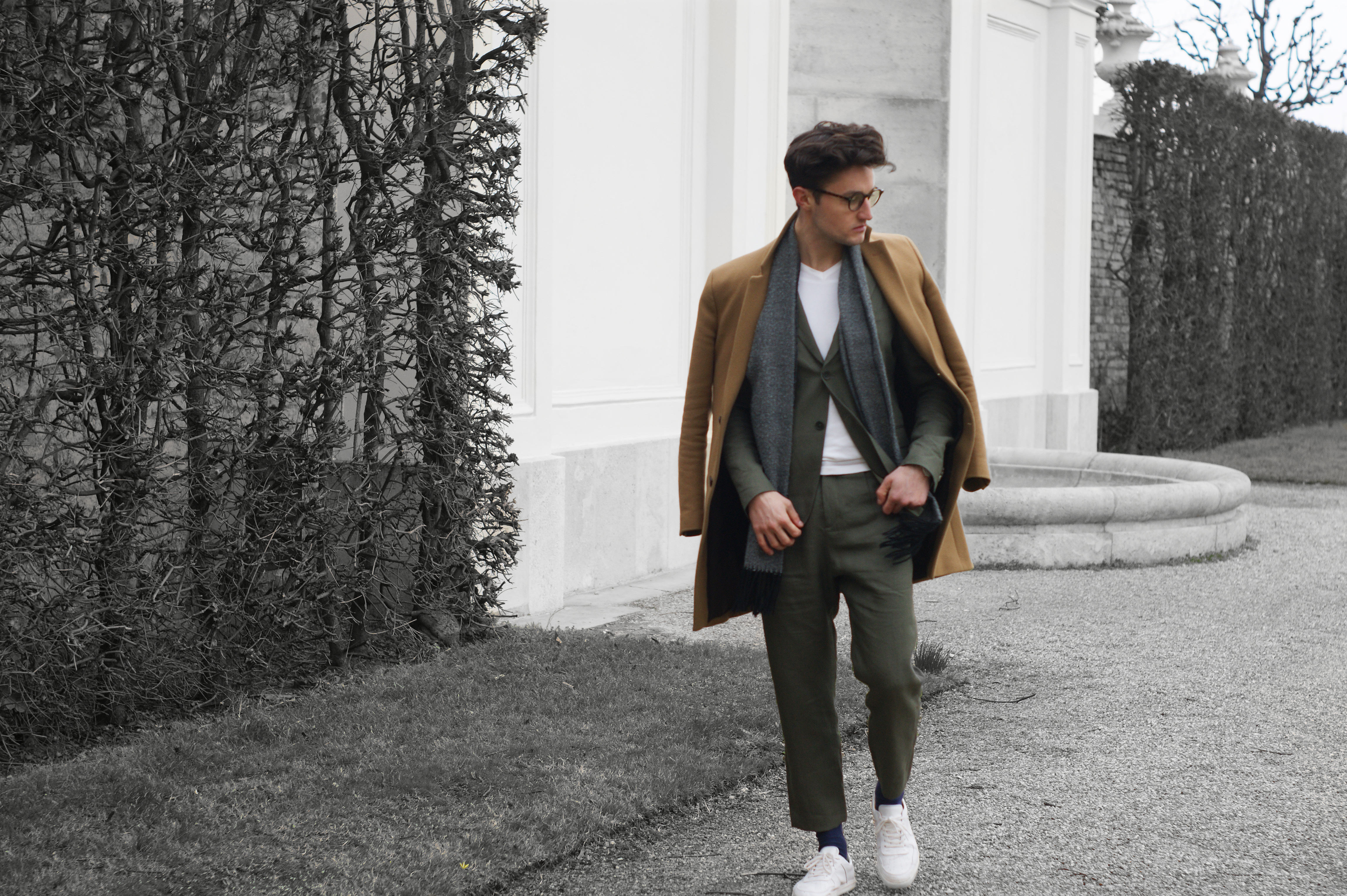The fashion blogger sarafi are showing their green suit outfit for the day. He is walking around in the park.
